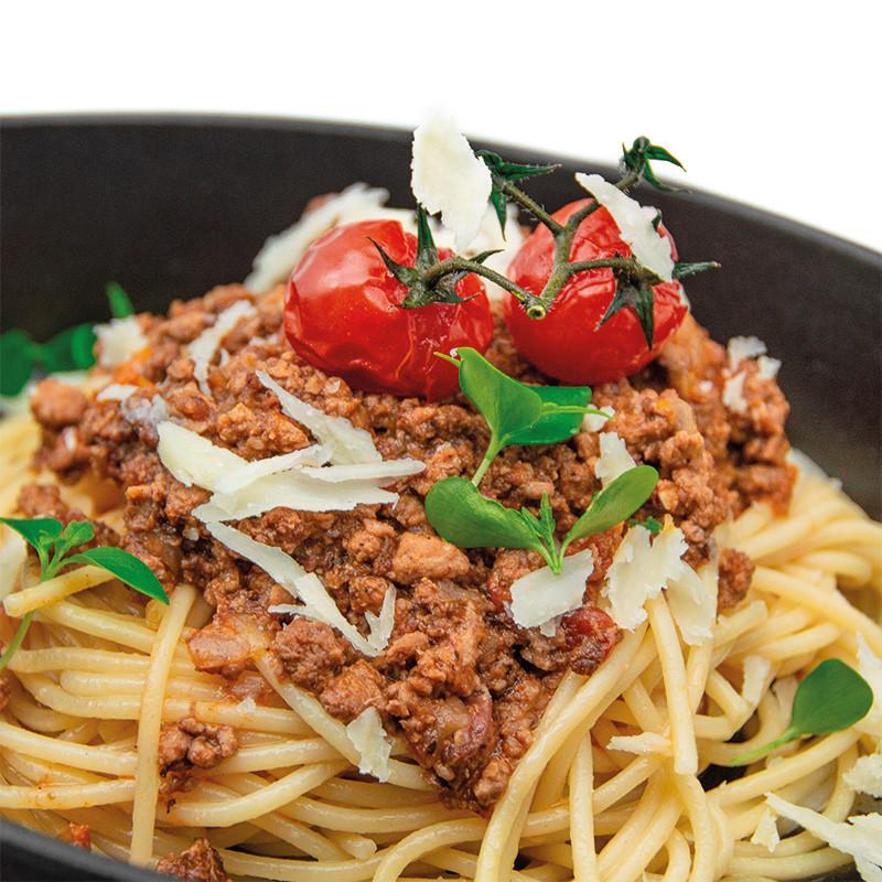 Angerichtete Bolognese Sauce auf Spaghetti mit Tomaten, Basilikum & Parmesan